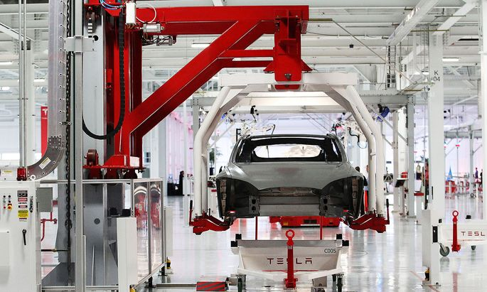 FILE PHOTO -- The body of a Tesla Model S is lifted by an automated crane at the Tesla factory in Fremont