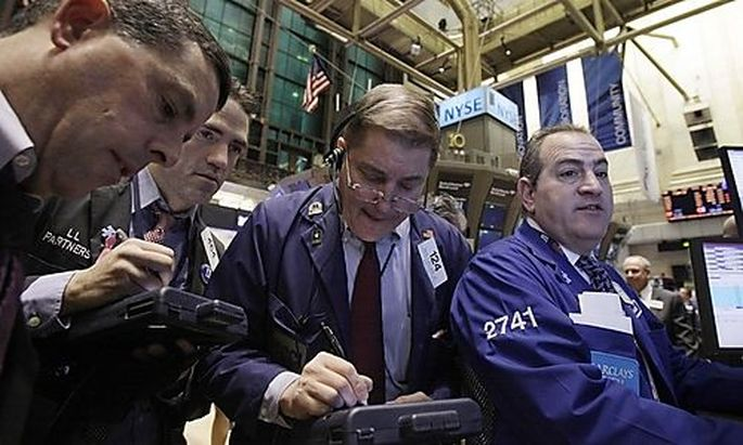 In this Feb. 1, 2011 photo, traders gather at a post on the floor of the New York Stock Exchange. (AP