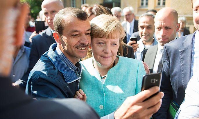 Ein Asylwerber schießt ein Selfie mit Kanzlerin ngela Merkel