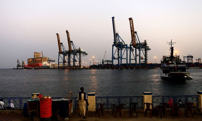 FILE PHOTO: A man stands opposite the modern port at the harbour in Port Sudan at Red Sea State