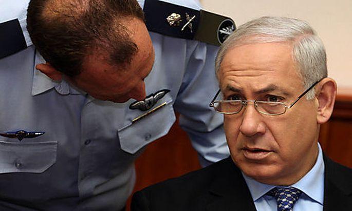 Israeli Prime Minister Benjamin Netanyahu, right, speaks with his military secretary Major General Yo