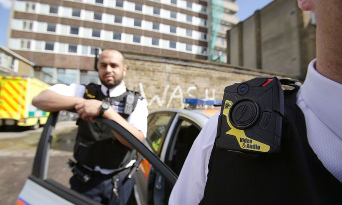 Police Constables Yasa Amerat and Craig Pearson pose for a photograph wearing a body-worn video camera, before a year-long trial by the Metropolitan police, at Kentish Town in London