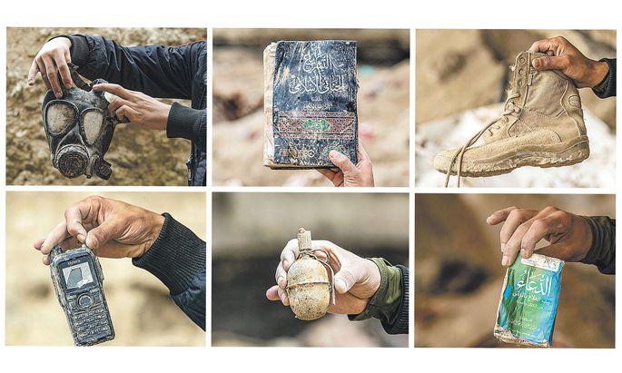 """Überreste des """"Kalifats"""". Kurdische Kämpfer zeigen Gegenstände, die sie in der früheren IS-Hochburg Baghouz – ein Jahr nach deren Eroberung – gefunden haben."""