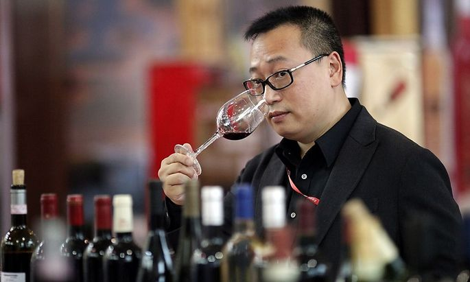 File photo of a man smelling a glass of red wine from Italy's Rosso Vino vineyard during the he 6th Shanghai International Wine Trade Fair