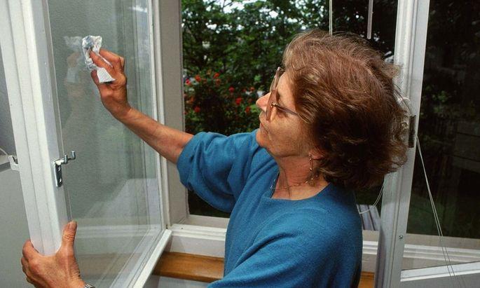 Frau putzt ein Fenster