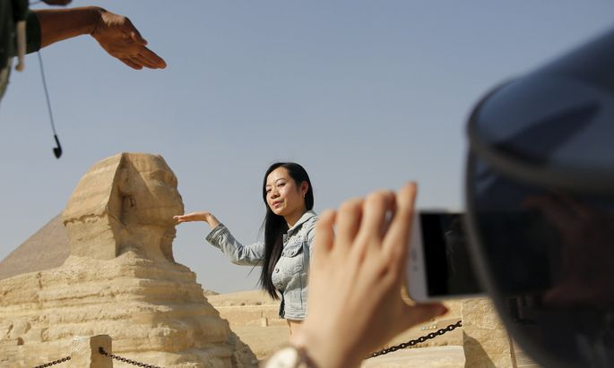 A Chinese tourist poses for a photo in front of the Sphinx at the Giza Pyramids on the outskirts of Cairo