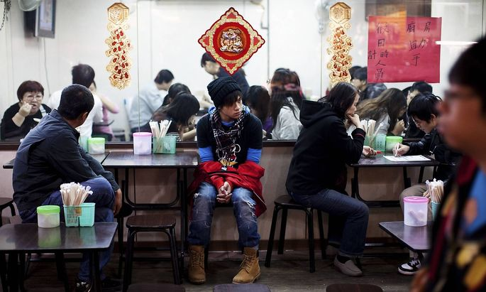 A teenage boy waits for his food at a street side restaurant at Shilin Night Market Taipei Taiwan