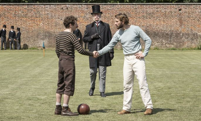 """Steinmetz Fergus Suter (Kevin Guthrie; l.) fordert mit der Arbeitermannschaft die """"feinen Pinkel"""" der Old Etonians um Arthur Kinnaird (Edward Holcroft) heraus."""
