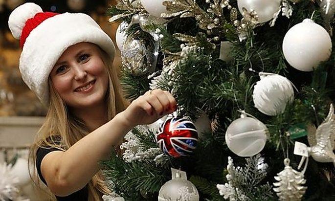 Selfridges employee Joanna Hetreed poses with a Union Jack Bauble, the best selling Christmas item, i