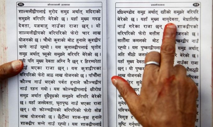 A Hindu holy man holds the holy book on his hand as he recites verses from the Swasthani Brata Katha book at the bank of River Saali in Sankhu during the first day of Swasthani Brata Katha festival in Kathmandu