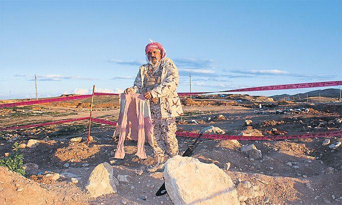 Haqi Ido mit dem Kleidungsstück eines Opfers aus dem Massengrab bei Herdan.