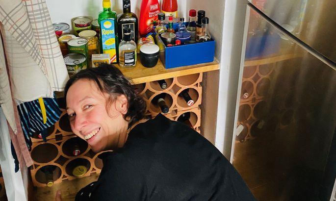 Ursula Strauss nützt die Zeit, um endlich einmal das Weinregal zu putzen.