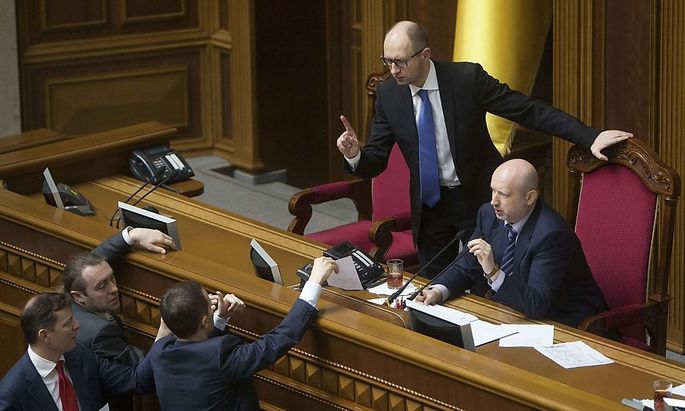 Ukrainian PM Yatseniuk and acting President Turchinov talk to deputies as they attend a parliament session in Kiev