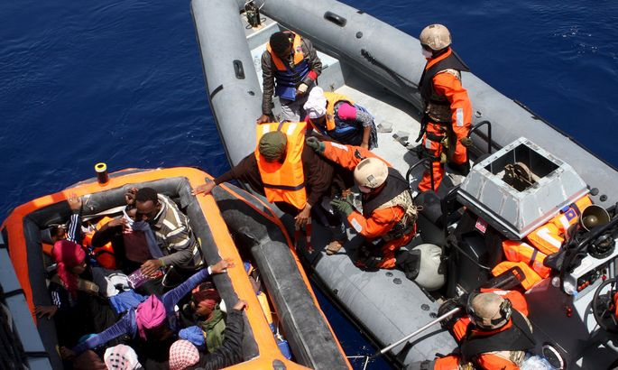 German servicemen assist some of around 200 rescued refugees boarding the frigate Hessen some 130 nautical miles off the Italian Lampedusa island