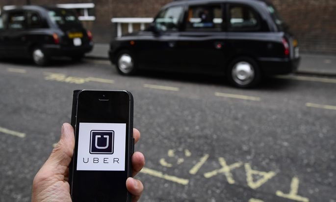 A photo illustration shows the Uber app logo displayed on a mobile telephone, as it is held up for a posed photograph in central London