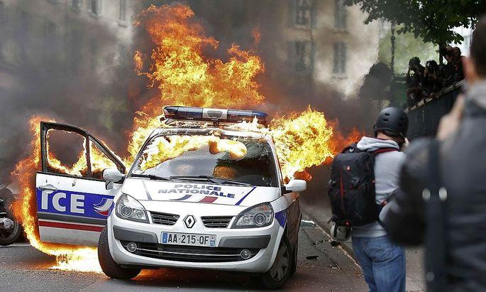 Demonstranten setzen ein Polizeiauto in Flammen.