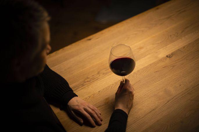 Symbolfoto zum Thema Alkoholismus: Eine Frau sitzt allein zu Hause an einem Tisch mit einem Glas Rotwein. Berlin, 23.01.
