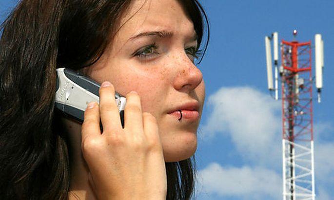 Frau mit Handy vor Handysendemast