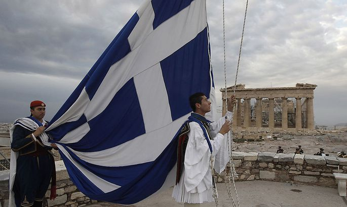 Greek Presidential Guards hoist the Greek flag in front of the Parthenon temple at the Acropolis hill in Athens