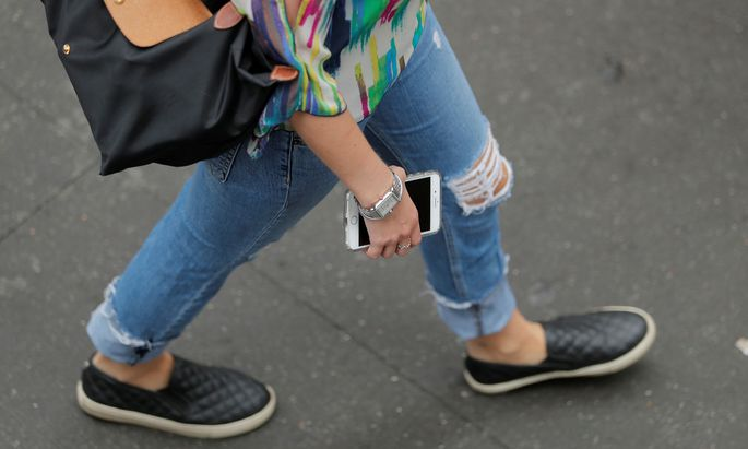 A woman holds an Apple iPhone as she walks on a street in New York