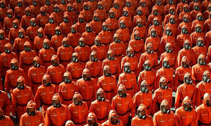 Orange Ganzkörperanzüge und Gasmasken - eine nordkoreanische Spezialeinheit sorgt für Spekulationen im Ausland.