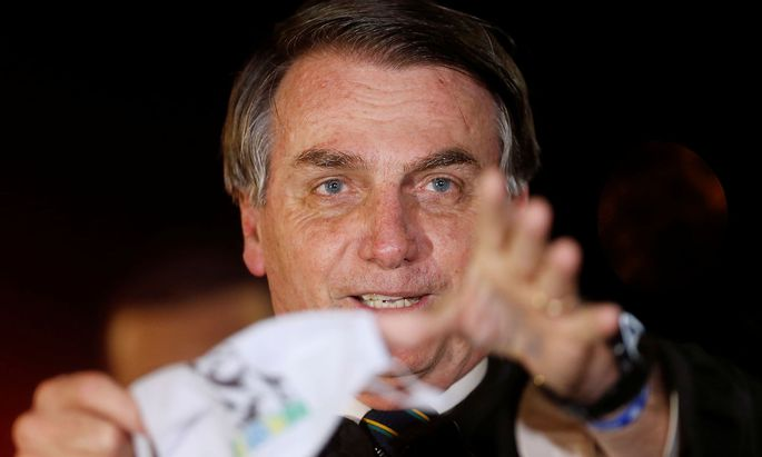 Brazil's President Jair Bolsonaro holds his protective face mask after removing it while speaking with journalists as he arrives at Alvorada Palace, amid the coronavirus disease (COVID-19) outbreak, in Brasilia