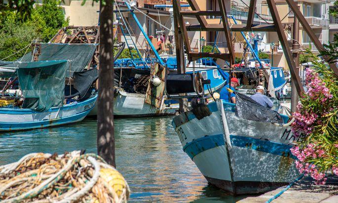 Gezeichnet von Salzwasser, mit dicken Netzen an Deck: Fischerboote am Kanal Richtung Lagune.