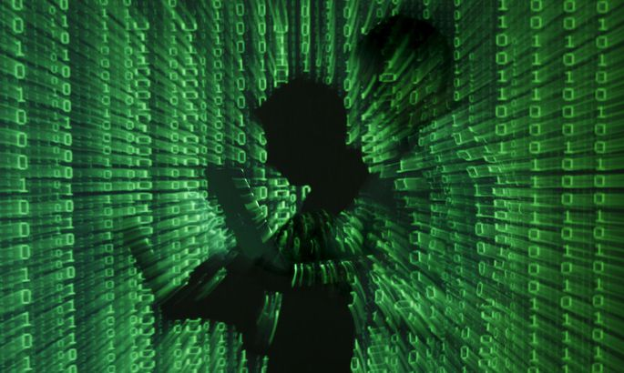 File picture shows projection of binary code on man holding a laptop computer in Warsaw
