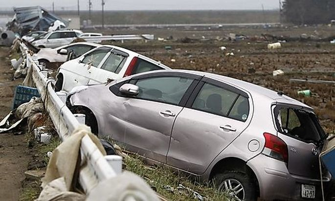 Damaged cars are seen at an area that was devastated by the March 11 earthquake and tsunami, in Watar