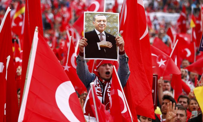 A supporter of Turkish President Erdogan holds up a picture during a pro-government protest in Cologne