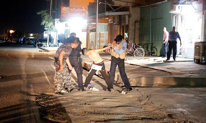 Irakische Sicherheitskräfte halten den jugendlichen Attentäter fest.