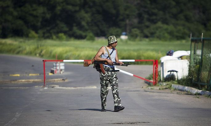 An armed pro-Russian separatist guards a border post abandoned by Ukrainian border guards at Chervonopartyzansk along the Ukraine-Russia border