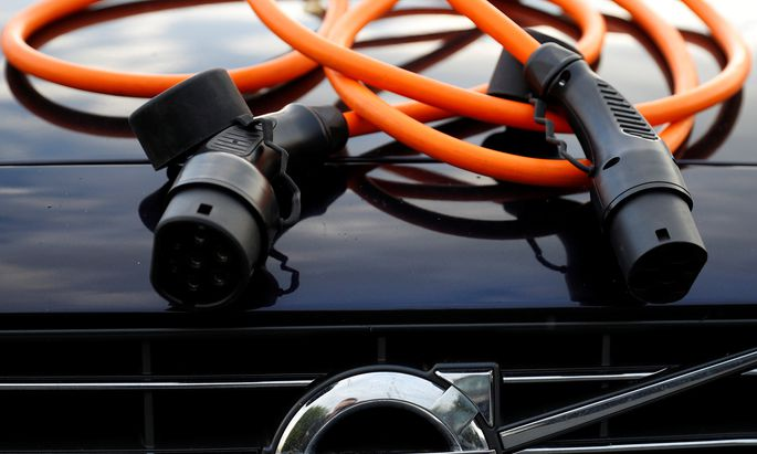 An electric vehicle charging cable is seen on the bonnet of a Volvo hybrid car in this picture illustration