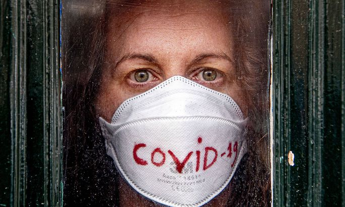 March 17, 2020, The Hague, Netherlands: A covid-19 coronavirus patient poses for photo looking out from her front door
