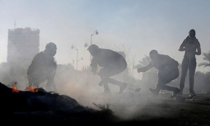 Palestinian protesters take cover during clashes with Israeli troops near the Jewish settlement of Beit El, near the West Bank city of Ramalla