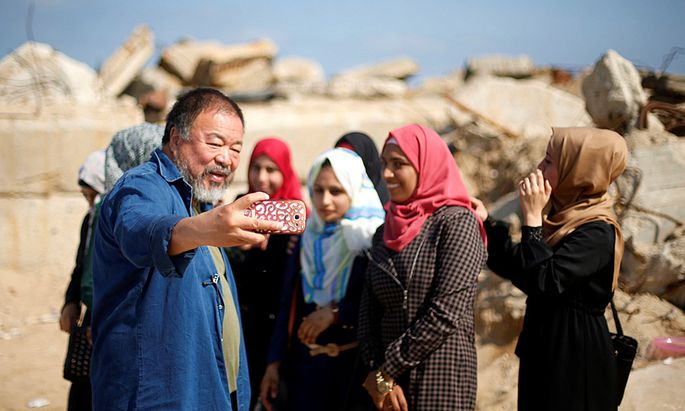Chinese artist Ai Weiwei (L) takes a selfie with Palestinian girls as he works on a documentary film on refugees, at the Seaport of Gaza City