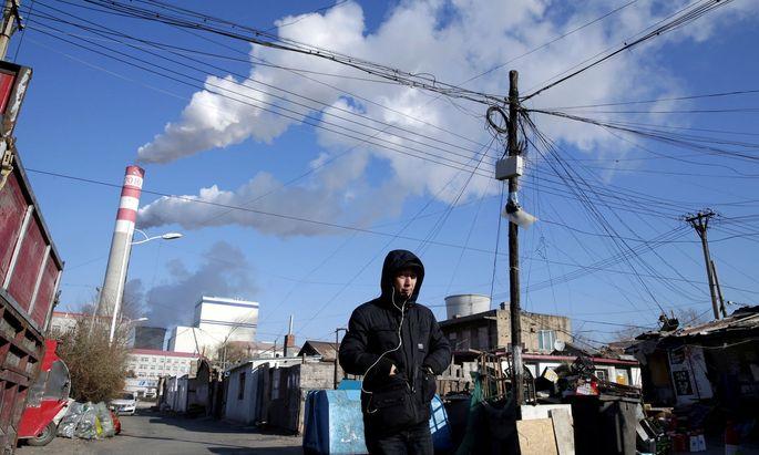 FILE PHOTO: A man walks near a coal-fired power plant in Harbin, Heilongjiang province, China