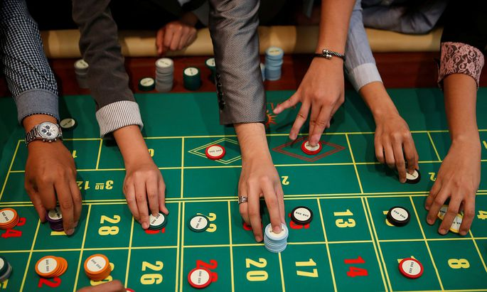 Casino dealers place their bets on a roulette table during training at Solaire Casino in Pasay city, Metro Manila