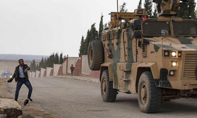 Schwieriger Syrien-Einsatz. Ein Mann bewirft ein türkisches Fahrzeug mit Schuhen. Die Türkei hat auch IS-Kämpfer eingefangen.