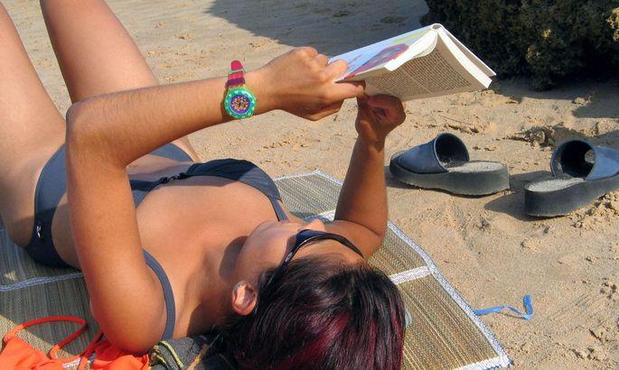 Frau liest Buch im Urlaub