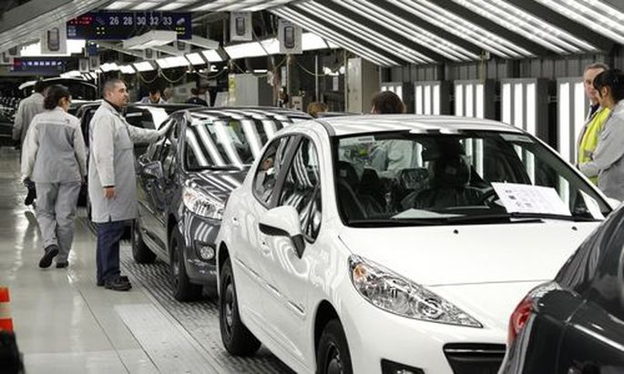 File photo of an employee working on the assembly line of the Peugeot 207 at the PSA Peugeot Citroen plant in Poissy
