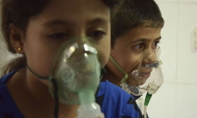 Children, affected by what activists say was a gas attack, breathe through oxygen masks in the Damascus suburb of Saqba