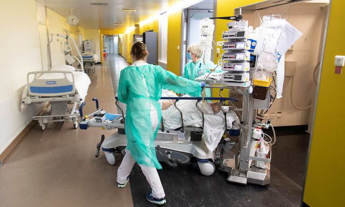 Medical workers push a bed with a patient in the emergency room unit at the CHUV in Lausanne