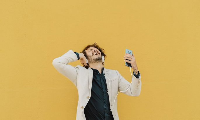 Businessman singing and dancing in front of yellow wall listening music with headphones and smartpho