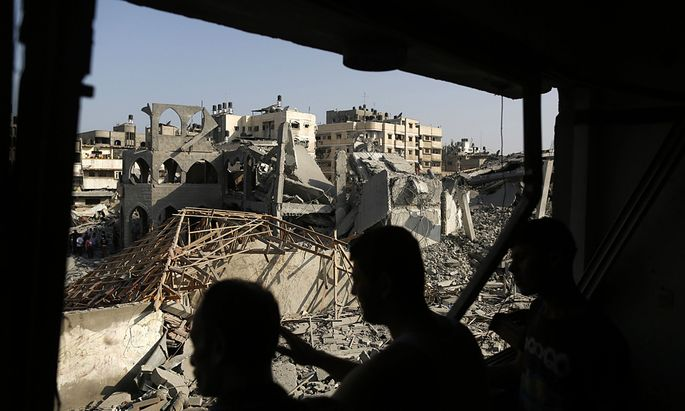 Palestinians look at the remains of a mosque, which witnesses said was hit in an Israeli air strike, in Gaza City