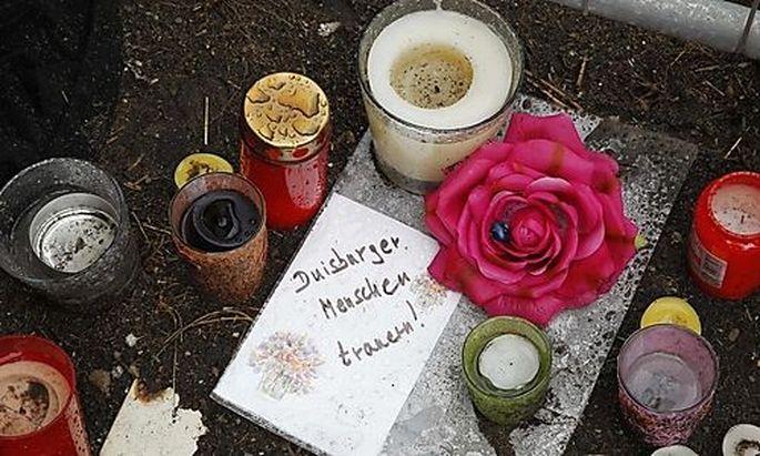 Zeichen der Trauer liegen am Montag, 26. Juli 2010, in Duisburg an der Stelle, wo bei der Loveparade