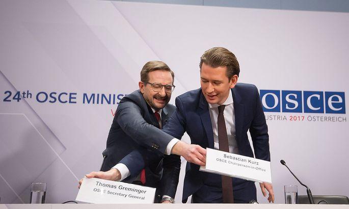 Sebastian Kurz und Thomas Greminger beim Schildertausch vor der kurzen Pressekonfrenz nach dem Abschlussd es OSZE-Treffens.