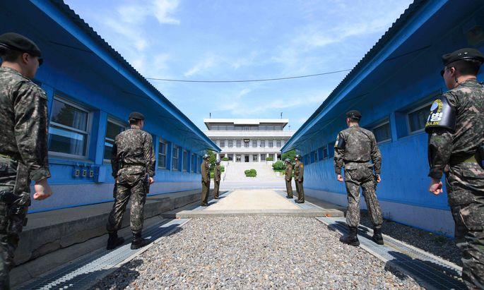 Südkoreanische (vorn) und nordkoreanische Soldaten stehen sich an der Demarkationslinie in Panmunjom gegenüber, wo Moon Jae-in und Kim Jong-un zusammenkommen.