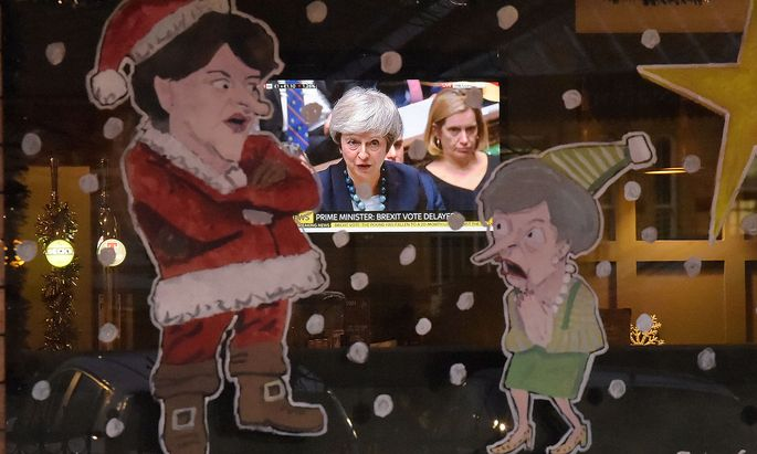 People in a bar watch Britain´s Prime Minister Theresa May during a debate in the house of Commons on television as a window is illustrated with DUP leader Arlene Foster as Santa Claus and Theresa May as a Christmas Elf in Lisburn
