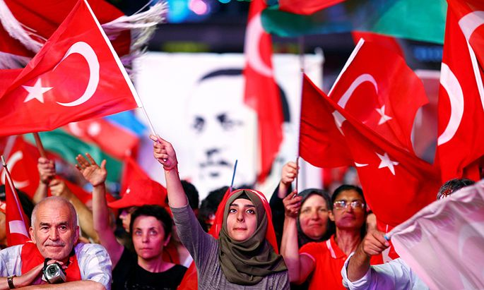 Supporters of Turkish President Erdogan wave national flags as they listen to him through a giant screen in Istanbul´s Taksim Square